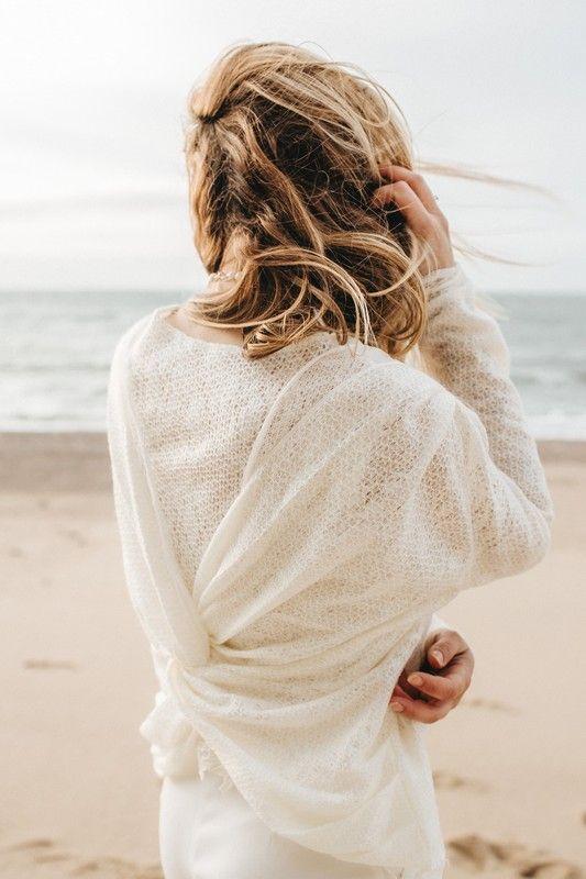 MADISON AIR DU TEMPS Légère de la tête aux pieds avec son débardeur en maille et soie. Complété par un pantalon fendu et resserré à la cheville, cet ensemble fluide aux tons blancs cassés, attisera la curiosité  des mariées au style décontracté. Pièce indispensable à adopter, la veste en cuir d'agneau velours aux tonalités naturelles et bordée de plumes aux épaules rappelle l'authenticité des matières.  En parallèle, le pull de laine fantaisie, croisé dans le dos apportera une touche de…