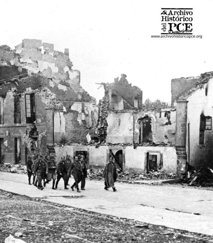 Según el PCE estas son Tropas franquistas recorren Belchite en octubre 1937. Toño Lucientes nos explica que no es Belchite, sino Bielsa. Lo que es cierto, visto el ancho de la calle y la forma de lo que se puede ver de lo que queda en pie de los edificios.