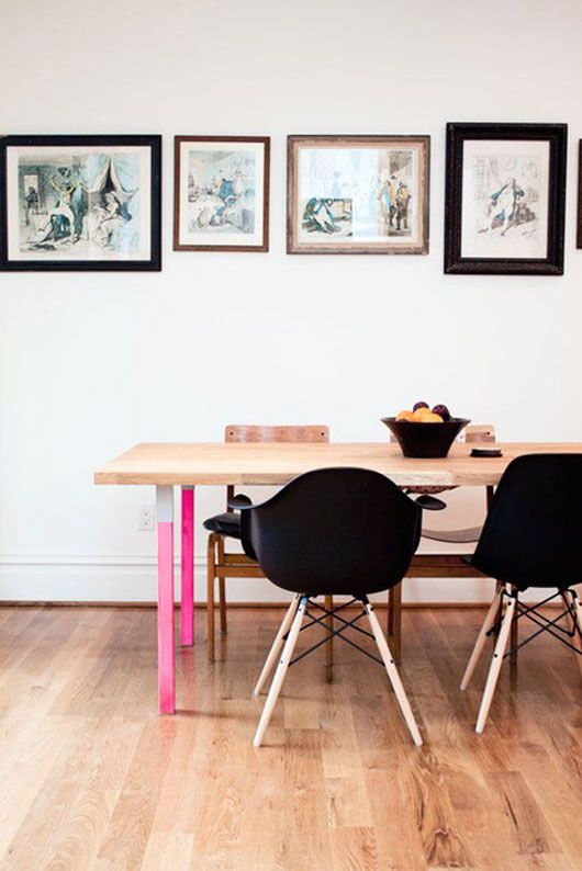 pink table legs, black eames chairs. also love the row of frames!