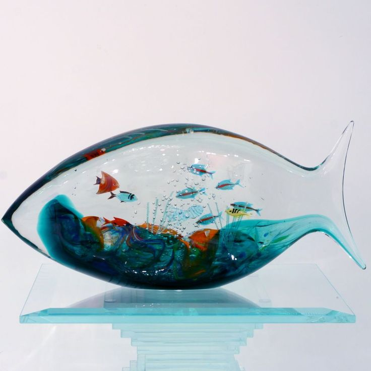 FISH SHAPED ACQUARIUM (by Romano Donà).  In this Murano glass aquarium the multicolored fishes are made separately.   In a second time the glass master melts them, under heat, between different leafs of crystal.   A long period of practice is necessary to learn the proper times and temperature to obtain a high level result like this.