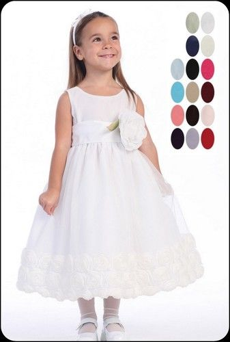 This elegant white dress is a twirly delight! Tulle overlays the sleeveless bodice and skirt. The waist features an interchangeable polysilk sash in your color choice with removable flower. Gorgeous floral ribbon flowers decorate the trim of the skirt making it perfect for your twirling beauty.