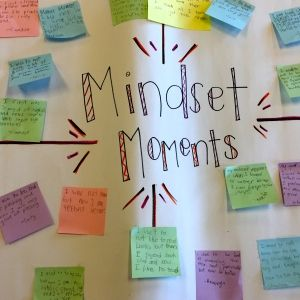A whiteboard with the words, Mindset Moments written on it has many colored post