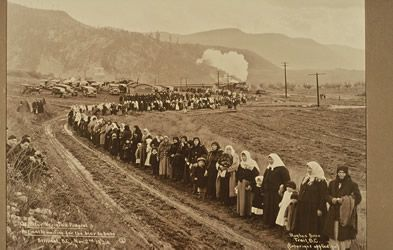 [ A crowd lines the road from Verigin's home, waiting for the bier to pass, Hughes Bros, Doukhobor Discovery Centre, Castlegar, BC  ]