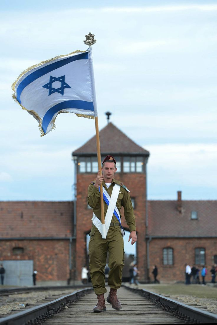 An Israeli Defense Force soldier marches with an Israeli flag through the main gate of the Auschwitz-Birkenau concentration camp on Holocaust Remembrance Day (2003)