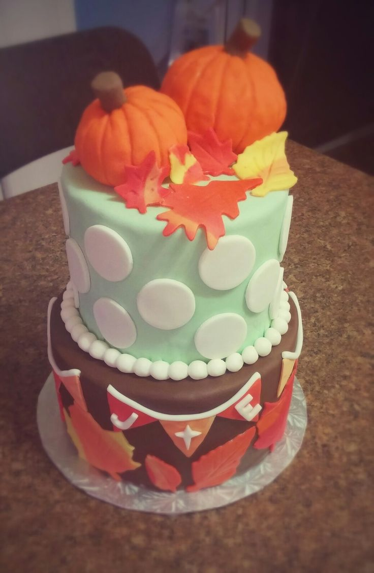 Fall cake ; vanilla cake at the bottom covered with chocolate fondant and fondant leafs and chocolate cake at the top topped with rice crispies pumpkins.