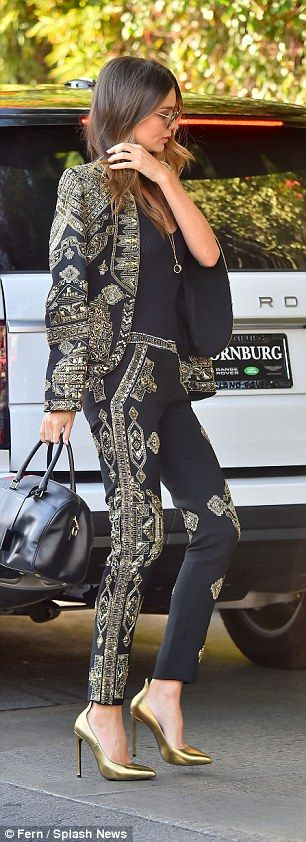 Style queen:Miranda gave the look a sexy, feminine twist by adding a pair of Saint Laurent gold 'thorn' pumps which she teamed with a $2,600 black duffle bag from the same designer