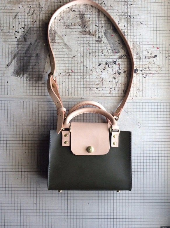 丁寧に作った持ち手やフタがポイントのシンプルなハンドバッグです。革の特性を活かすため、バッグ本体には1枚革を贅沢に使った繋ぎ目の無いシンプルなデザイン。どなたでもお使いいただける普段使いに適したハンドバッグです。使いやすい事を重視し、物を取り出しやすくするためマチをたっぷりと取りました。※バッグは本体の色のみお選びください。バッグのパーツはすべてヌメ(ベージュ)革となります。 ※レザーカラーはブラウン、ダークブラウン、ヌメ(ベージュ)、レッド、モスグリーン、ブラックの6色です。糸カラーはポリエステルの茶、濃茶、べージュ、赤、濃緑、黒となります。糸カラーのご要望がなければ革の色に合わせた色で製作いたします。糸や金具のカラーなど変更のご要望は別途メールなどでご連絡くださいませ。※受注生産ですので2週間以内に製作完了次第発送いたします。<仕様>内ポケット×1素材:牛革金具:真鍮※ドイツホックは真鍮メッキとなります。パーツ:ヌメ革ステッチ:総手縫いサイズ:バッグ本体 16×23.5×10cmベルト 100-65cm(5cm間隔で7つベルトホールが空いています。)
