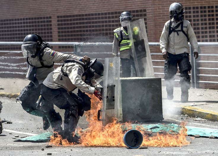 Riot policemen are attacked with Molotov cocktails by demonstrators in Caracas on April 8, 2017.