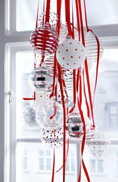 Décoration fenêtre pour Noël avec une suspension de boules de Noël blanches et rouge et transparentes accrochées avec du ruban de satin rouge