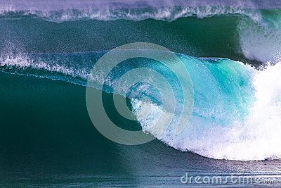 Ocean wave with perfect lip shape starts pitching towards a shallow shoreline. The hollow wave is peeling with color and shape and the white water ball rolls inside the  wave. Telephoto lens photo image for a close up moment on this section of the crashing or pitching wave