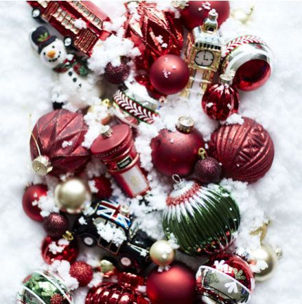 Red, silver and green Christmas baubles on snowy backdrop