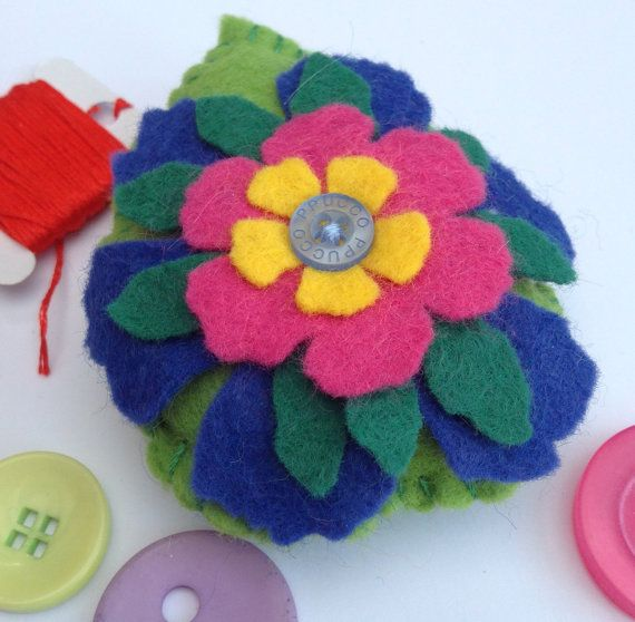 This is a hand sewn, leaf shaped, felt pincushion with a flower motif and button detail. It can be used as a pincushion or a decoration to brighten up any home. This item measures approximately 10 cm x 8 cm and is made from high quality wool felt. Flower is cut using a Tim Holtz die, layering complementary colours of blue, green, pink and yellow to make the a beautiful flower motif, finished with a button at the centre. The bottom layer is stitch on to the base cushion, while the other…
