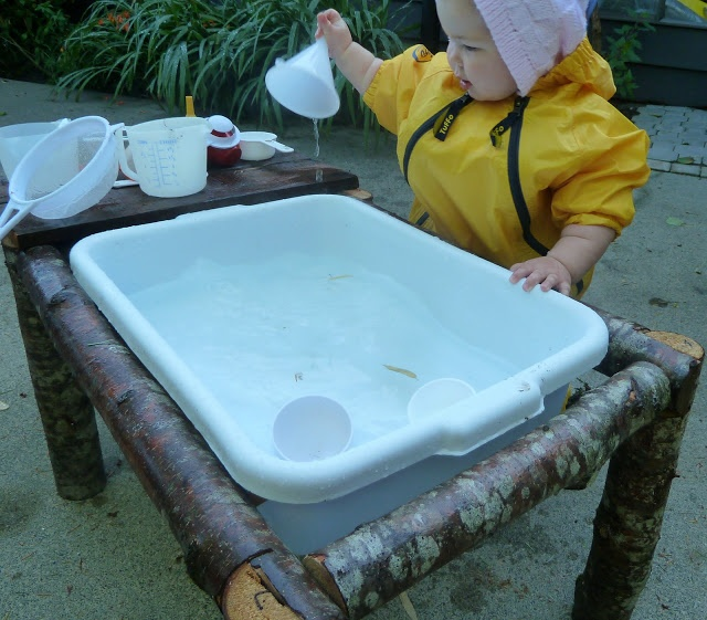I like the size of this sand table for infants/toddlers. I also like that the frame is wood (round, rough surface) compared to the smooth surface of the water bin. There are a few real-life tools to use to play with the water - measuring cups, sieves, funnel - which children would see at home.