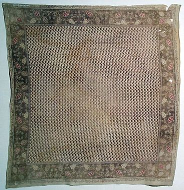 Halskläde 1780-1820 Västergötland, Kållands hd, Tådene.  Halskläde av tunn bomullslärft med blocktryckt mönster. I mittspegeln stramt småfigurigt upprepningsmönster med trekantig figur, kantbård med liten blad-och blomslinga. Ljusa färger i rosa och brunt på oblekt bottentyg.