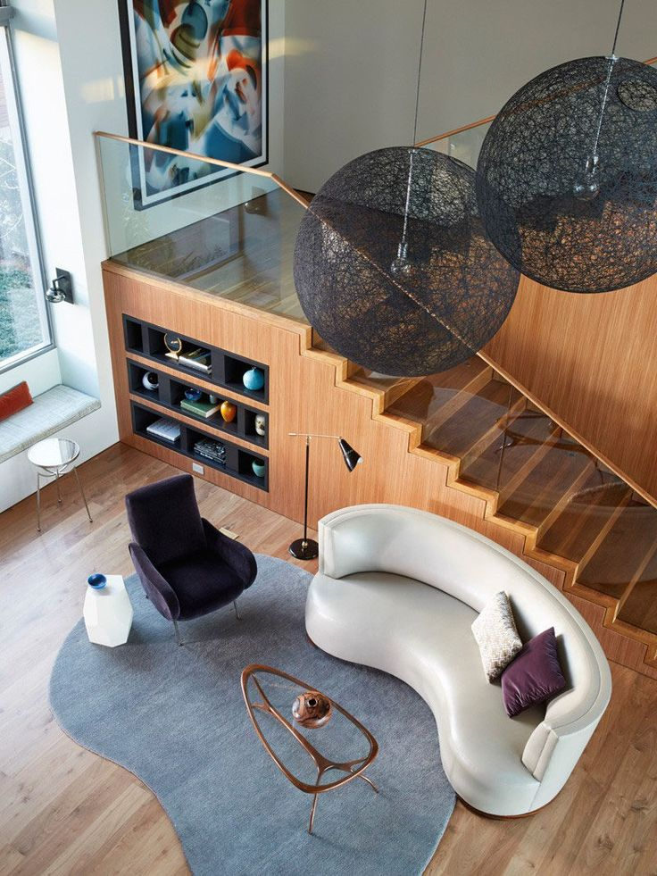 Interior Design Ideas - 17 Modern Living Rooms As Seen From Above | Soft curves on the rug, coffee table, armchair, and couch give this living room area a relaxing feel that compliments the clean lines of the stairs and built in shelving.