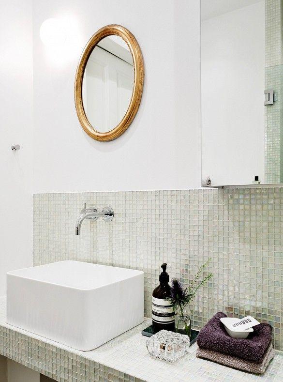 Bathroom with mosaic tile backsplash and bronze oval mirror.