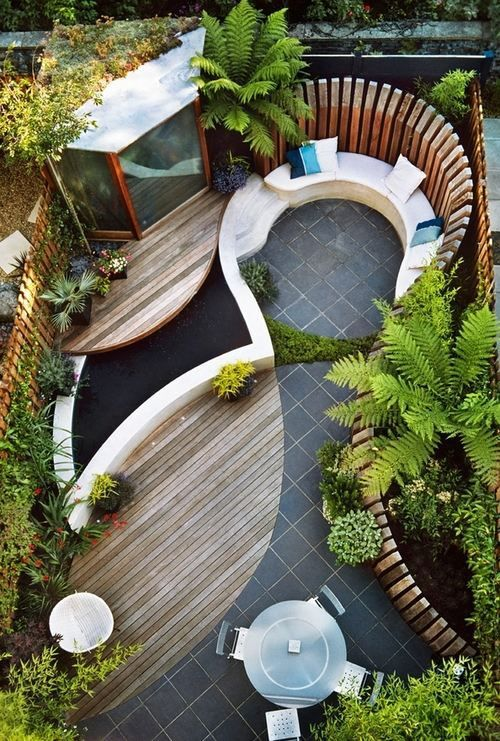 Amazing outdoor living space with circle-seating, a small pond, and lots of green - great use of a small space