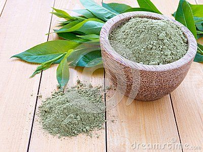 Henna powder pile and green leaves on the wooden background