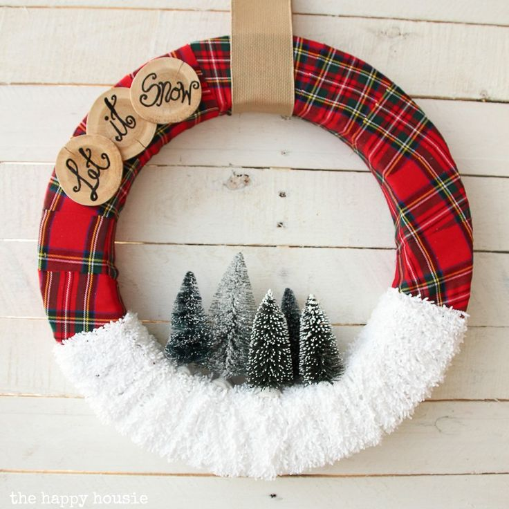 Adorable and easy to make Let it Snow Christmas Wreath featuring plaid and yarn snow and bottle brush trees along with wood slice pieces.