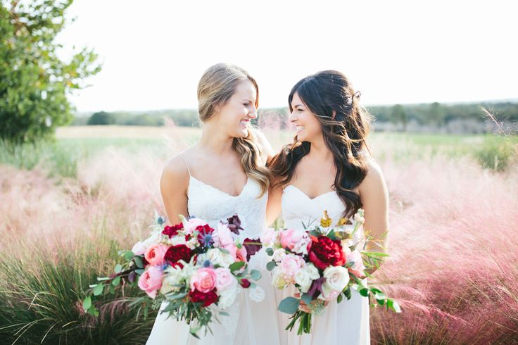 in a field of fall pink and ivory grasses, a bride and her bridesmaid hold loose and lush fall bouquets of red peony, pink garden rose, blush spray rose, pink ranunculus, blue thistle,peach stock, white astilbe, quicksand rose, eucalyptus and vines.