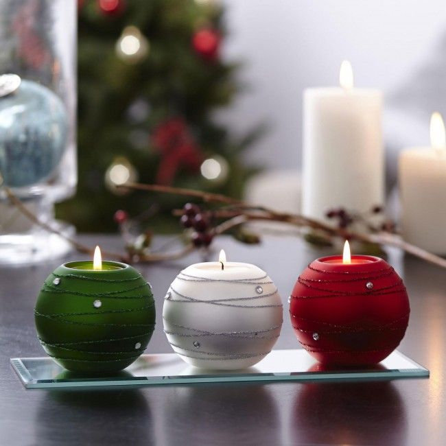 Make your holidays merry and bright with these glamourous tealight holders. They are a perfect way to add charm and holiday elegance to your home. Three beautifully decorated ornaments sit on a bevelled glass tray that sparkles and reflects light. Enhance any room with a festive holiday atmosphere.