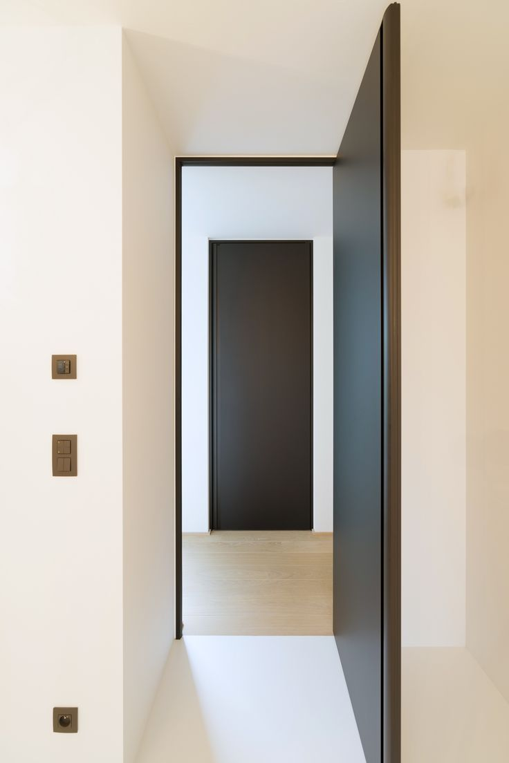 Zwarte deur van vloer tot plafond, volledig op maat gemaakt door het belgische merk Anyway Doors. Innovatief maatwerk met praktische meerwaarde! De deuren zijn onderhoudsvriendelijk en krasbestendig, ze worden alleen met hightech materialen gemaakt zoals geanodiseerd aluminium en Resopal Massiv (volkern).