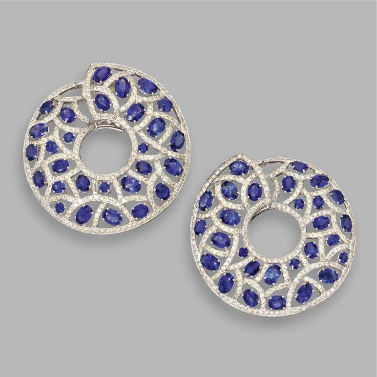 PAIR OF SAPPHIRE AND DIAMOND EARRINGS, MICHELE DELLA VALLE The openwork hoops set with 56 oval sapphires weighing approximately 24.00 carats, framed by numerous round diamonds weighing approximately 7.50 carats, mounted in 18 karat white gold, maker's mark, numbered 10829.