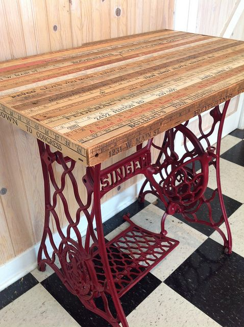 An antique Singer treadle sewing machine base finds new life as a table with the…