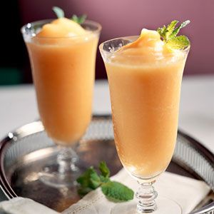 Christmas Blossom (2 cups fresh or frozen peach slices 1/4 cup sugar 3/4 cup vodka 3 tablespoons peach schnapps Ice cubes Garnish: fresh mint sprigs)