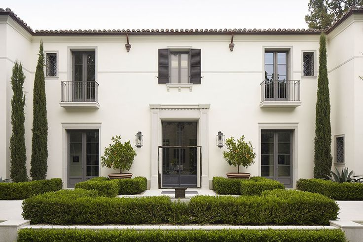 DANIEL C. CUEVAS | SLIDESHOW. white stucco home with greenspace. floor to ceiling window pane doors