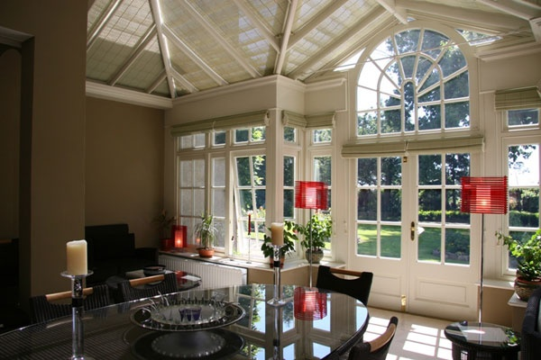 A stunning wooden conservatory with Georgian window design complete with conservatory roof blinds and conservatory window blinds.