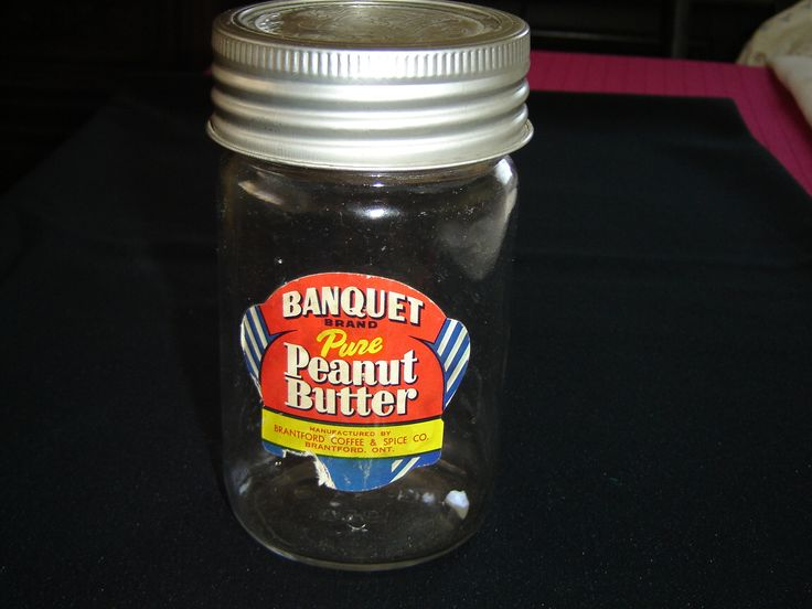 """Originally contained Banquet brand Peanut Butter The label reads: BANQUET BRAND Pure Peanut Butter MANUFACTURED BY BRANTFORD COFFEE & SPICE CO. BRANTFORD, ON This item measures 5 5/8"""" (14.3 cm) high x 2 7/8"""" (7.3 cm) in diameter The reverse of the jar is embossed: MADE IN CANADA a crown symbol CROWN the bottom of the jar is embossed: 6 a square, a D in a diamond, 0 1960"""