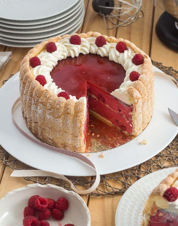 Charlotte à la framboise composée de couches de biscuit à la cuillère maison, de framboises fraîches et de mousse fruitée à la framboise. Elle est recouverte d'une gelée à la fraise et décorée de chantilly à la vanille et de framboises fraîches.