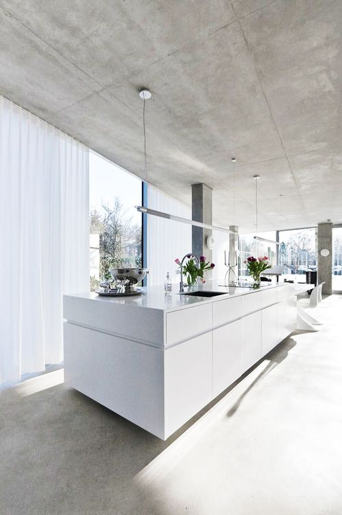 Low gloss cabinets are subtle and suit the matte  concrete flooring