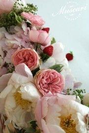 różowe piwonie, róże, hortensje. goździki, zieleń i truskawki w wiązance na stole pary młodej
