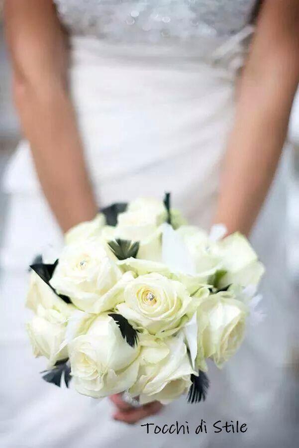 Bouquet di rose bianche e piume bianche e nere con punti di luce attraverso strass