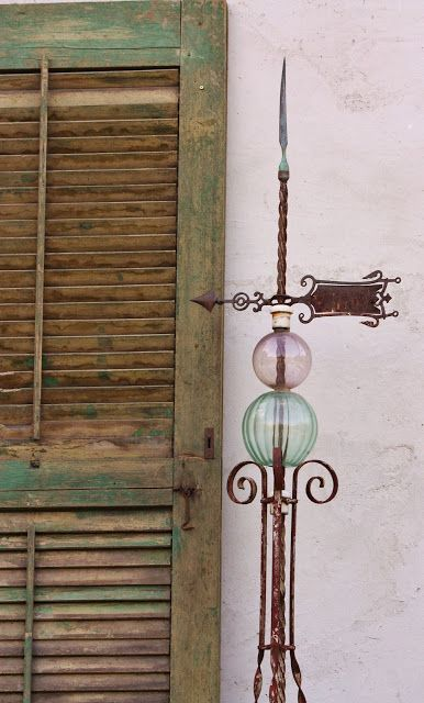 """Antique iron lightning rod with copper finial and antique amethyst and green glass globes.  I love how the colors in the lightening rod mimic the colors in the old shutter."""