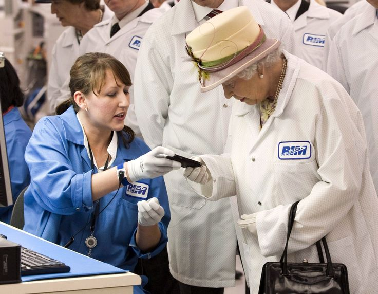 Queen Elizabeth II is shown a new Blackberry phone by electronics assembler Elvira Dulic as she tours Research in Motion, Canada, 2010.