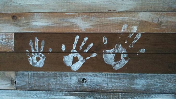 Perheen kädenjäljet mökin etikalla sävytetyssä seinässä