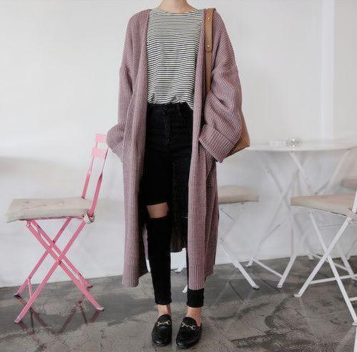 Elle porte un cardigan à manches longues et lisses avec un jean à la cuisse et une chemise de bronzage