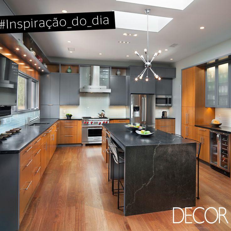 Esta cozinha contemporânea conta com lustre, fogão, coifa e geladeira em inox.  Para tornar o espaço mais aconchegante, a madeira, o piso laminado e o jogo de luzes contrastam com parte do armário em tom chumbo.