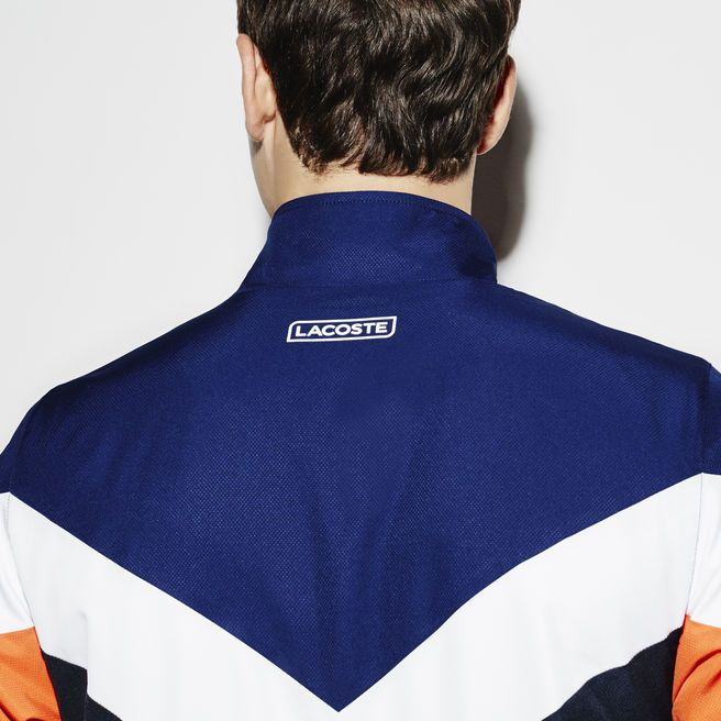 Forget power suits: you power this shiny taffeta tracksuit! Lacoste Sport Tennis provides the V-shaped colorblocks, colored piping and elasticized finishes.