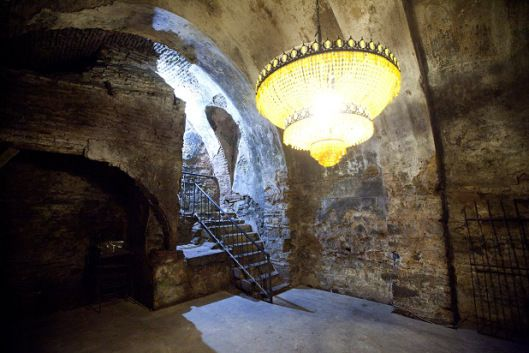 """basdogan_halicilik_tempo3Sultanahmet'in yeraltı zenginliğinin iyi bir örneği… Bugünkü halini alması için, 600 kamyon moloz çıkartılmış. Başdoğan Halıcılık'ın arka tarafında ve ziyarete açık. Giriş kısmı, merak uyandıran cinsten: Yeşilliklerle sarmalanmış yüksek duvarlar, ortada karanlığaaçılan bir geçit… Geçidin ötesi; Büyük Saray'ın mahzenleri. Bir tabelada şöyle diyor: """"Şu an Büyük Saray'da bulunuyorsunuz."""