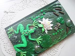 Сегодня я хочу вам показать, как можно украсить обложку блокнота или записной книжки полимерной глиной. Будем лепить болото :). Для этого нам понадобится: 1. Блокнот. 2. Полимерная глина — разные оттенки зеленого, коричневая, белая, желтая. 3. Жидкая пластика. 4. Стеклянные декоративные шарики. 5. Металлические элементы (шапочки для бусин). 6. Бусины. 7. Стек с шариком. 8. Зубочистки. 9.…