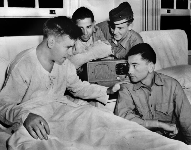 Marine Al Schmid, left, photographed in the hospital, was blinded when a grenade exploded in his machine gun pit; he continued firing until relieved. For his courage he received the Navy Cross.