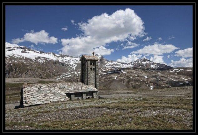 De col de l'Iseran is de hoogste verharde bergpas in de Alpen. Op de top die 2770m hoog is krijg je een mooi panorama van de besneeuwde bergen. Op de voorgrond de kapel Notre-Dame de l'Iseran. - Alpen en de Jura