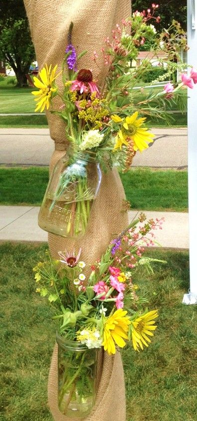 mason jars filled with wildflowers decorating a wedding arbor... how cute would this be hanging from our pergola?!