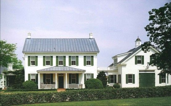 White farmhouse style house with barn, green shutters and doors