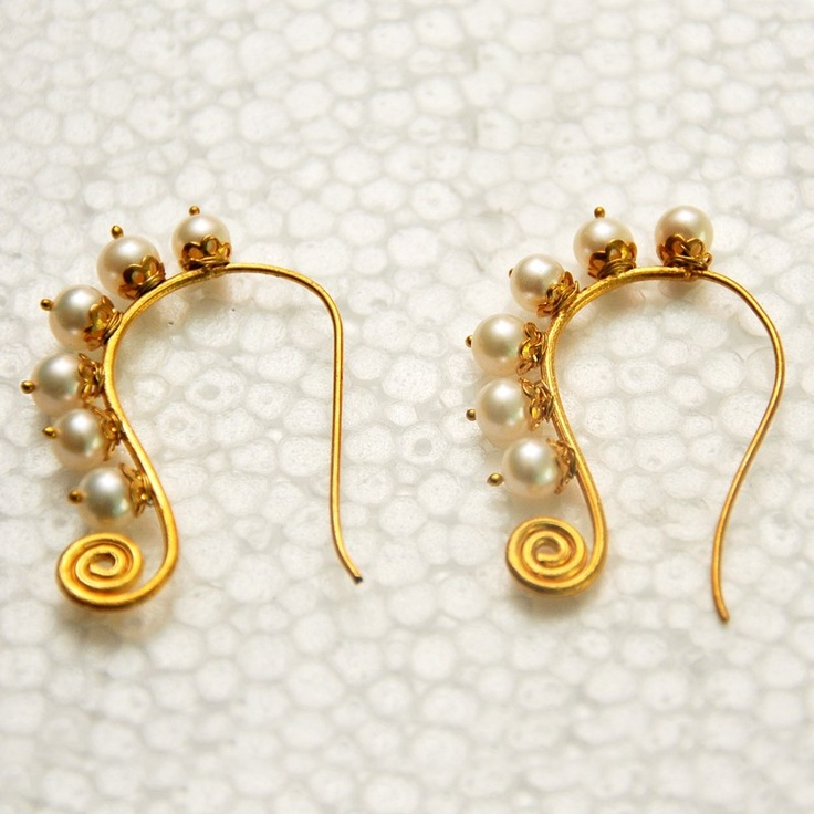 Six perfect fresh water pearls sit snuggly on individual flower pots that grow from a stem that coils on one end and curves gracefully on the other. This light weight earring is 4 micron gold plated ,heat treated for that earthy colour.