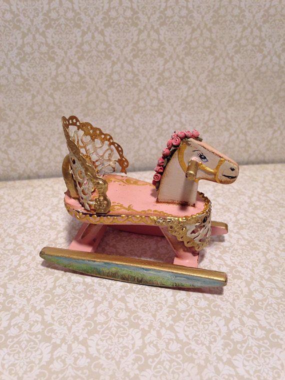 Caballito balancin de madeta policromada de color rosa, bordes en dorado, flores en relieve realizadas artesanalmente